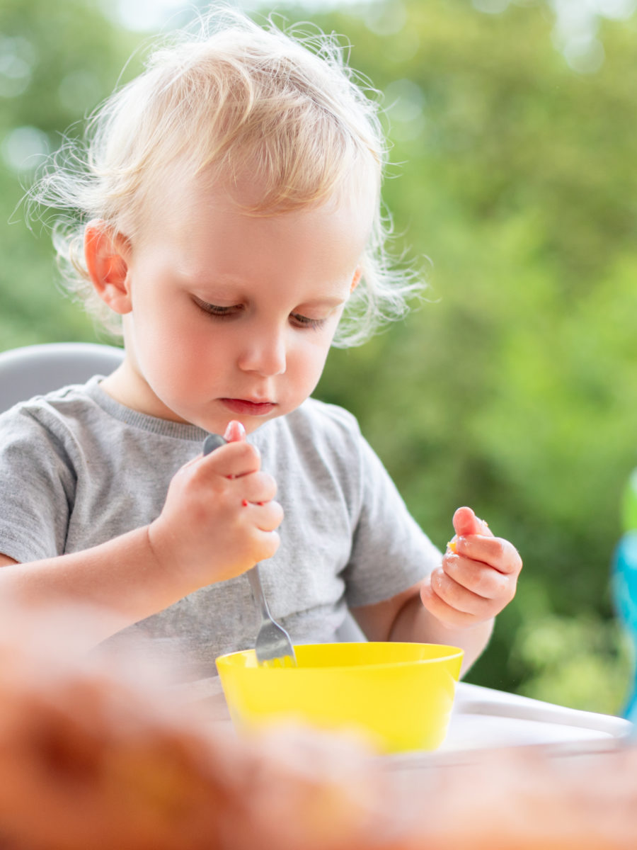 Focused and polite baby child eating lunch outdoor